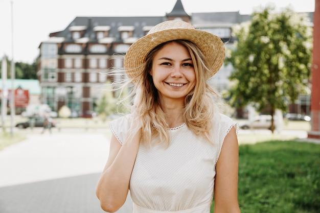 Красивая блондинка идет по городу. женщина в белом платье и соломенной шляпе