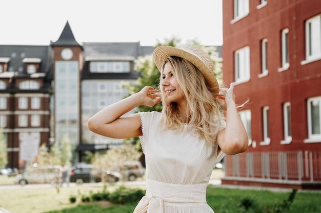 美しい金髪がヨーロッパの街を歩きます。白いドレスと麦わら帽子の女性、彼女は笑顔で幸せです
