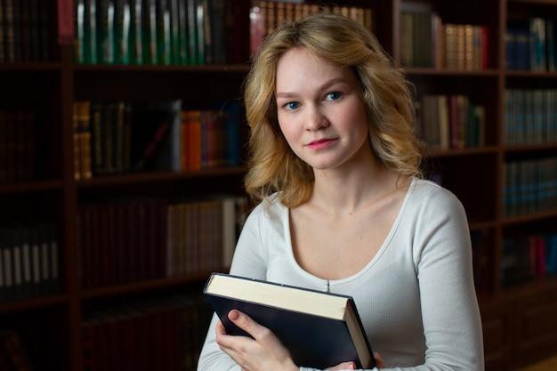 白いジャケットに青い目をした美しいブロンドは、開いた本を持ってカメラをのぞき込みます。図書館で情報を探している学生