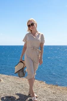 드레스를 입은 아름다운 금발의 여성이 해변을 따라 걷고 있습니다. 여름 휴가, 여행 및 관광. 화창한 날에 휴식.