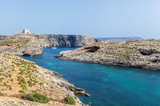 청록색 맑은 물과 노란색 석회암으로 이루어진 높은 바위 해안이 있는 아름다운 푸른 석호
