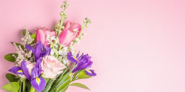 Красивый букет живых цветов на розовой пастельной поверхности