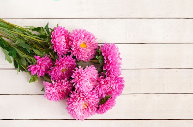 Красивый букет розовых астр лежит на белом деревянном фоне, копией пространства
