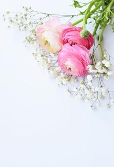 Красивый букет из розовых лютиков (лютиков) с нежными белыми цветами гипсофилы на белой поверхности.