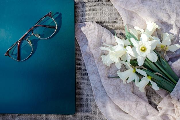 Красивый букет весенних белых нарциссов цветов, книга, очки на фоне холста