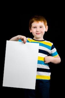 아름다운 소년은 그의 손에 깨끗한 흰 종이의 큰 시트, 귀여운 빨간 머리 아이의 클로즈 업 초상화를 보유하고 있습니다