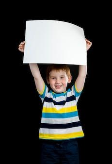 아름다운 소년은 그의 손에 깨끗한 흰 종이의 큰 시트, 귀여운 빨간 머리 아이의 근접 촬영 초상화를 보유하고