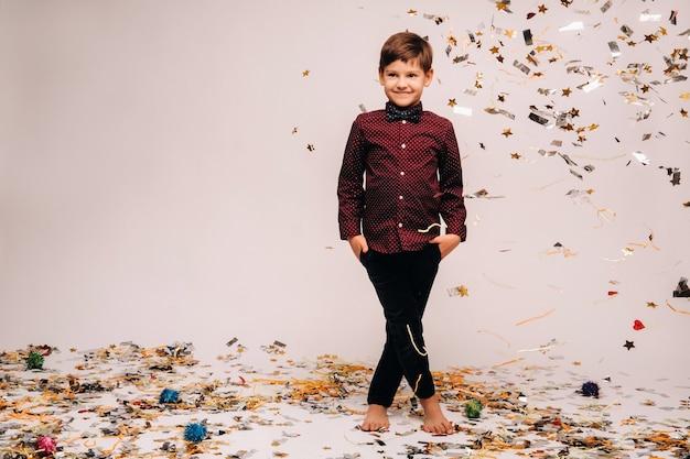 美しい少年が立って、灰色の背景に紙吹雪が彼の上に落ちます。
