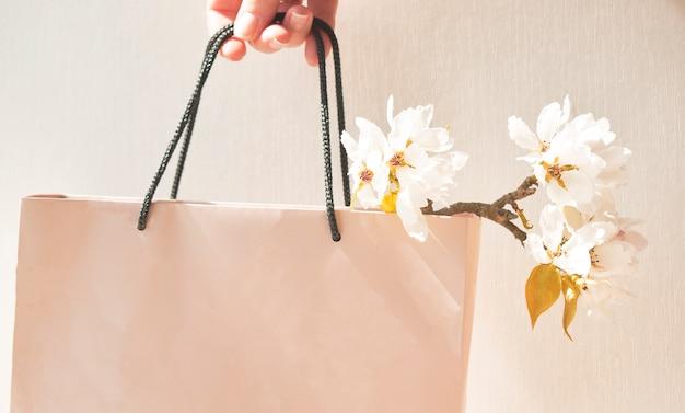 女性の手で紙袋に春の花の美しい枝。フローラルでロマンチックなムード。女性への贈り物。女性の日のお祝い。