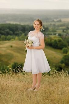 白いドレスを着た美しい花嫁が自然の中に立って、彼女の手にウェディングブーケを持っています。