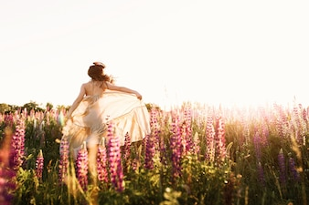 A beautiful bride in wedding dress is dancing alone in a field of wheat.