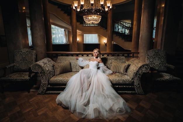 아름다운 신부가 고급스러운 소파에 앉아 있습니다. 하얀 웨딩 드레스에 아름 다운 모델 소녀입니다. 좋은 아가씨의 여성 초상화입니다. 머리를 가진 여자.