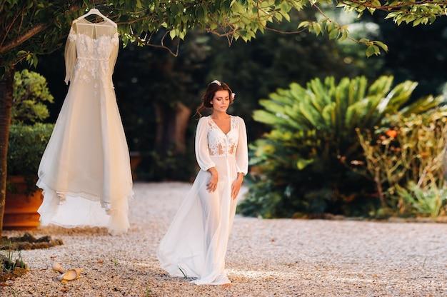 イタリアの別荘の隣にある私室の服装のウェディングドレスの隣に美しい花嫁が立っています。トスカーナの花嫁の朝。