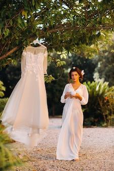 イタリアの別荘の隣にある私室の衣装でお茶を飲みながらウェディングドレスの隣に立っている美しい花嫁。トスカーナの花嫁の朝。