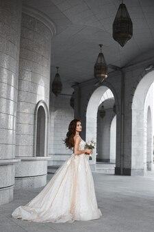 Красивая невеста в роскошном кружевном свадебном платье позирует на открытом воздухе романтический портрет ...