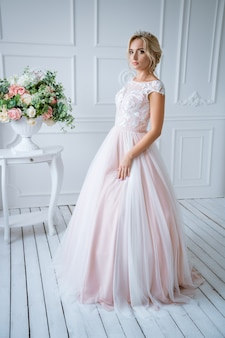 髪とメイクの美しい花嫁は、花で明るい装飾の繊細なピンクのウェディングドレスに立っています