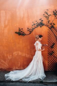 Красивая невеста с приятными чертами лица в свадебном платье фотографируется в провансе.