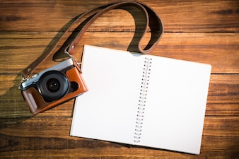A beautiful brown fashioned camera next to notepad