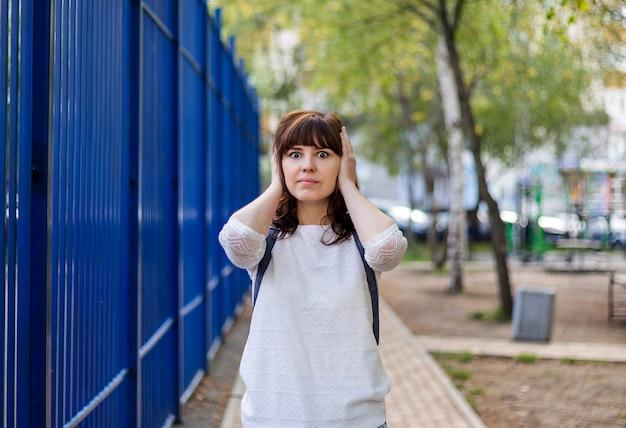 아름다운 갈색 머리 소녀는 그녀의 손으로 그녀의 귀를 덮었습니다. 나는 아무것도들을 수 없습니다. 항의의 몸짓. 흰색 재킷을 입은 소녀가 거리에 서 있습니다.