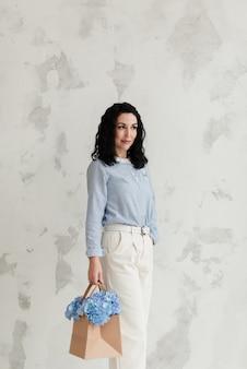 파란색 스웨터와 흰색 바지에 아름다운 갈색 머리 소녀는 푸른 꽃과 가방을 보유
