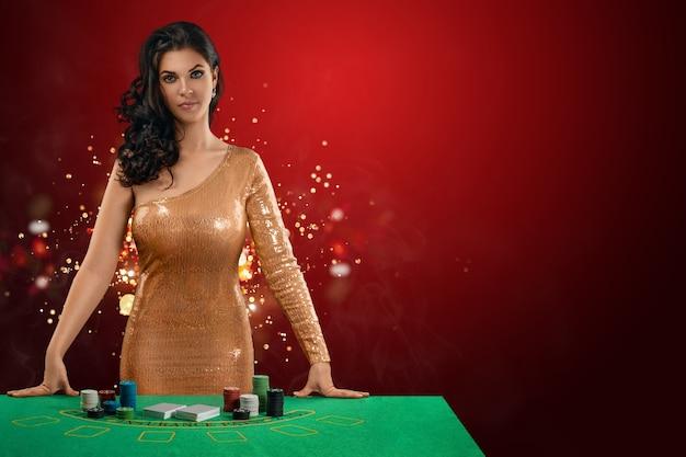金色の光沢のあるディーラードレスを着た美しいブルネットの少女がギャンブルテーブルの前に立っています