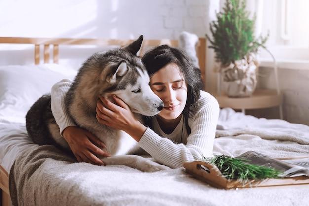 Красивая девушка брюнетка лежит на кровати с белой хаски дома. солнечное утро
