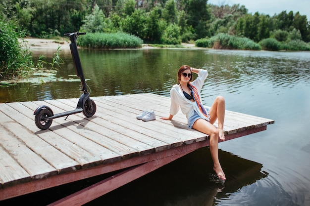 아름다운 갈색 머리 소녀가 전기 스쿠터 옆 강 근처의 나무 다리에 달려 있습니다. 생태와 전기 운송의 개념입니다.