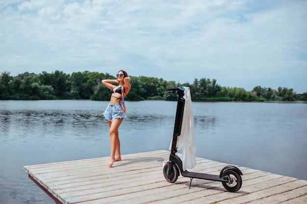 水着姿の美しいブルネットが木製の橋で日光浴をし、近くにスクーターがあります。エコロジーとヘルスケアのコンセプト。高品質の写真