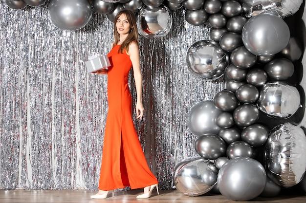Красивая брюнетка в красном платье с подарком в руках ходит на фоне серебряных украшений и шаров. празднование новогоднего или рождественского корпоратива. мягкий фокус.