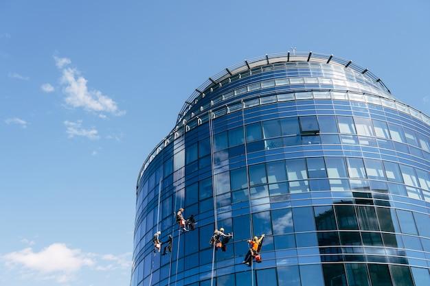 青い鏡張りの窓がある美しいビジネスセンター。窓拭きサービスは、窓を汚れから掃除します