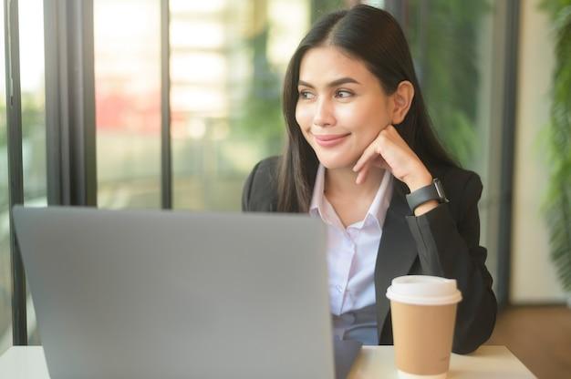 Красивая деловая женщина анализирует финансовые данные через компьютер, пьет кофе в кафе. образ жизни деловых людей. технологическая концепция. Premium Фотографии