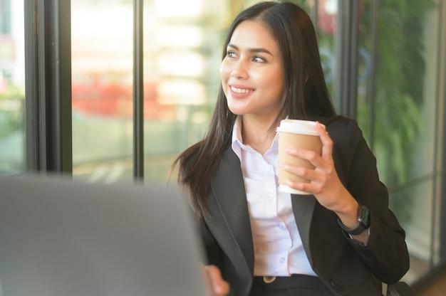 Красивая деловая женщина анализирует финансовые данные через компьютер, пьет кофе в кафе. образ жизни деловых людей. технологическая концепция.