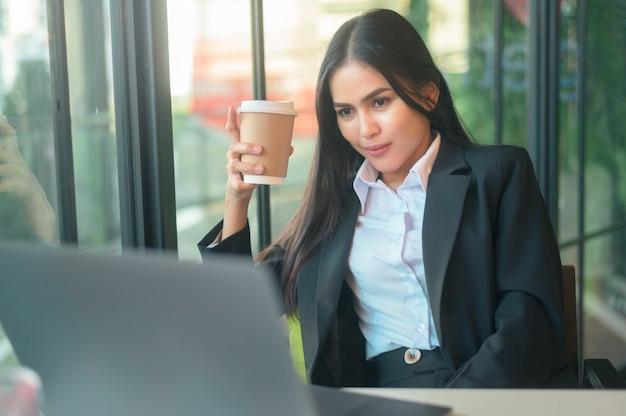 美しいビジネスウーマンがコンピューターを介して財務データを分析し、喫茶店でコーヒーを飲んでいます