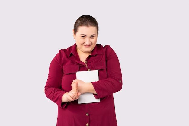 큰 크기의 종이 옷을 입은 빨간 드레스를 입은 아름다운 여성 사업가가 회색 배경을 느슨하게 하는 방법