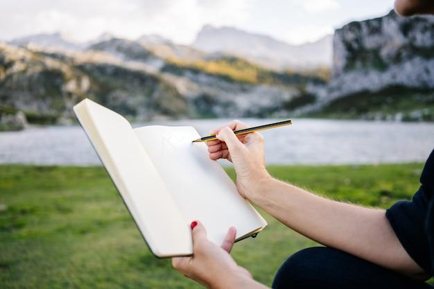 美しい白人金髪女性は書き込み、湖と山の風景でメモ帳に描画します