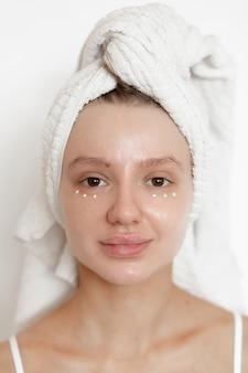 Красивая кавказская женщина с полотенцем на голове и каплями крема под веками