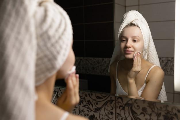 Красивая кавказская женщина с полотенцем на голове в ванной после душа смотрится в зеркало, чистит кожу ватным тампоном и улыбается. концепция ухода за кожей.