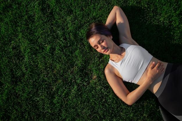 흰색 티셔츠를 입은 아름답고 명랑하고 쾌활한 여성이 공원의 녹색 잔디에 누워 웃고 있습니다. 화창한 여름 날 잔디에서 편안한 행복 한 여자. 평면도. 대형 배너