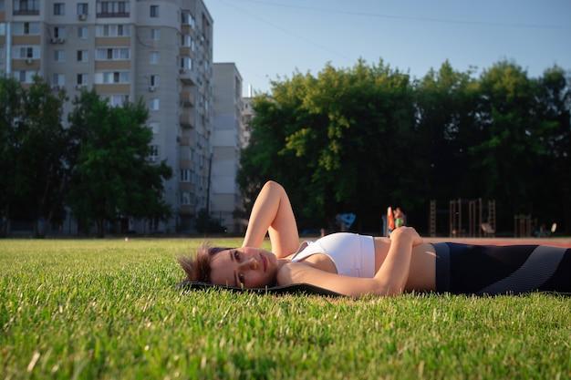 아름답고 명랑하고 쾌활한 여성이 공원의 푸른 잔디밭에 누워 웃고 있습니다.