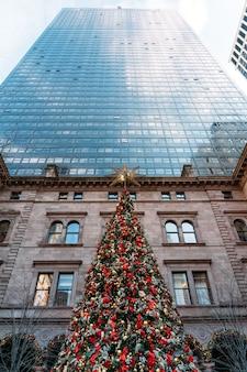 Красивая новогодняя елка, украшенная множеством красных и желтых шаров с большими небоскребами.