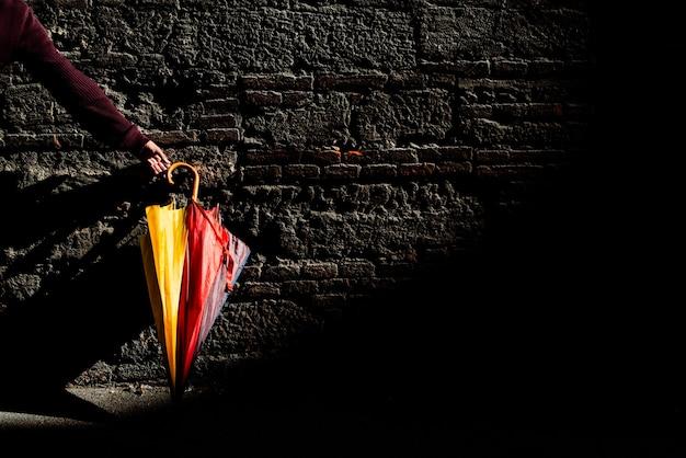 Красивый цветной зонт, сложенный в сложенном виде, стоит у кирпичной стены, освещенной первыми после дождя лучами солнца.