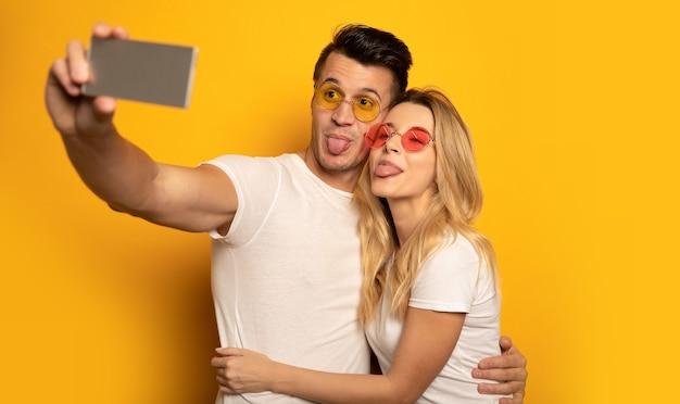 Красивая пара в разноцветных солнцезащитных очках обнимает друг друга и улыбается, делая селфи на своем смартфоне