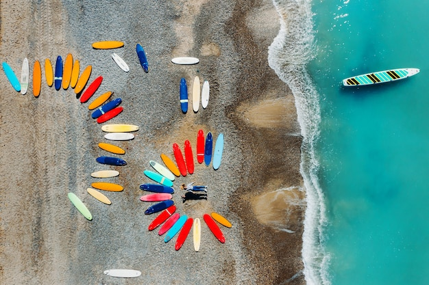 아름다운 커플이 서핑 보드 옆에있는 프랑스 해변에 누워 쿼드 콥터에서 촬영하고 있으며 많은 서핑 보드가 비정상적으로 해변에 누워 있습니다.