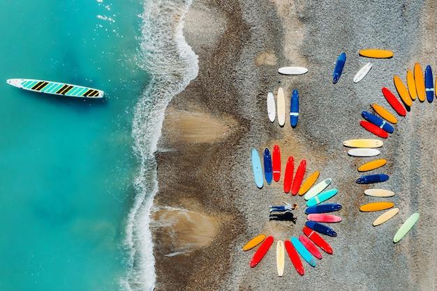 아름다운 커플이 서핑 보드 옆에있는 프랑스 해변에 누워 쿼드 콥터에서 촬영하고 있습니다.