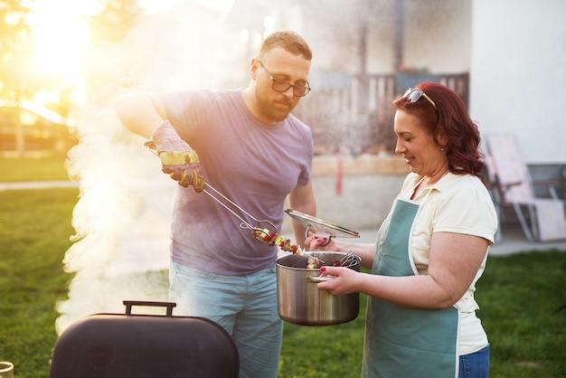 아름다운 커플이 고기와 야채를 그릴에서 꺼내 냄비에 넣고 있습니다.