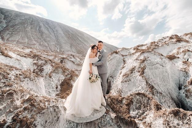 Красивая пара влюбленных позирует в белой соляной горе.
