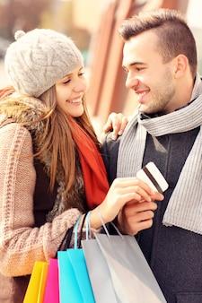 Красивая пара делает покупки с помощью кредитной карты в городе