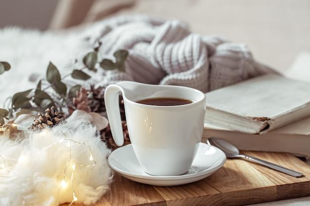 Красивая чашка горячего напитка среди деталей домашнего декора.