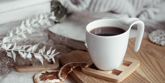 Красивая чашка с чаем или кофе на деревянной подставке. концепция домашнего уюта.
