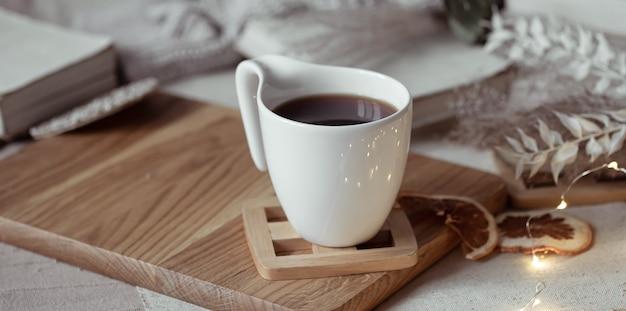 나무 스탠드에 차 또는 커피와 함께 아름다운 컵. 가정의 편안함 개념.